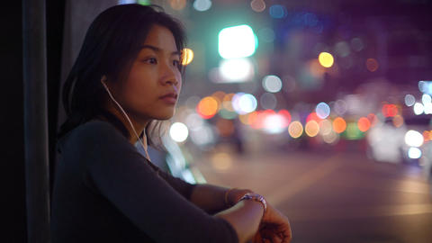 Asian Woman using smart phone with headset in night city Footage