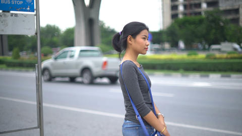 Young Asian Woman waiting at bus stop Footage