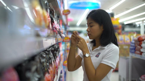 Woman is testing smell of household chemicals at supermarket Footage