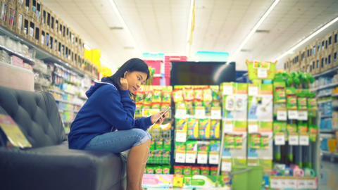 Young Asian Woman is listening music in supermarket Footage