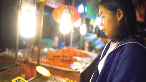 Young Asian girl buying barbecue seafood at night food market Footage