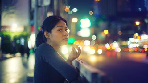 Asian Girl eating ice cream on street of night city Footage