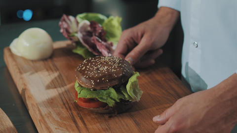 Cooking chief put skewer into wheat bread hamburger and take bite Footage