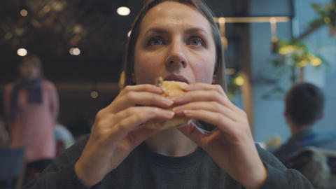 Woman eats a hamburger in a cafe Live Action