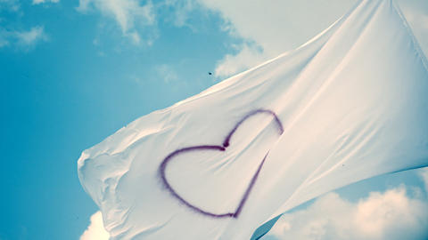 White flag with heart symbol, waving on wind Footage