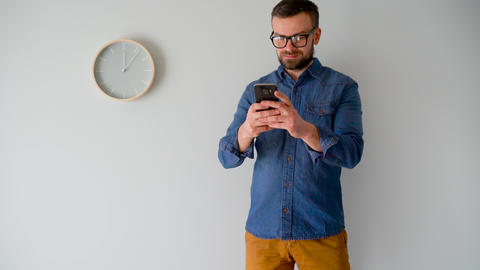 Bearded man using smartphone against a gray wall with a clock Footage