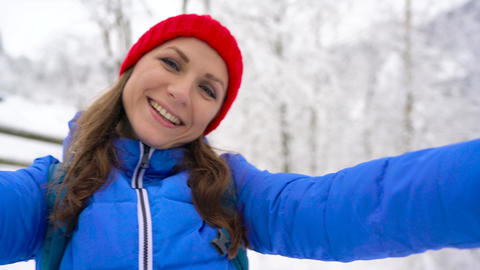 Young cheerful woman holds a camera and shoots herself in a snow-covered Footage