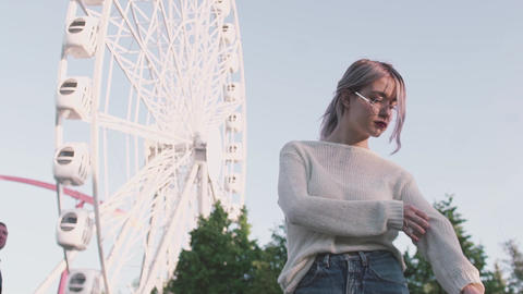 Pretty girl in glasses standing under observation wheel amusment park Footage