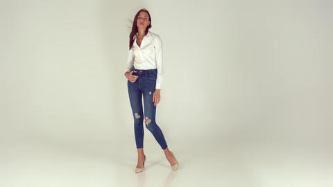 A young and happy girl in stylish jeans on a white background Footage