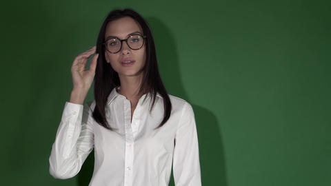 Young beauty woman in glasses. Woman in round glasses on a bright green Footage