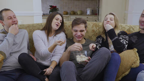 Young people eats popcorn and watches movie at home Footage