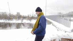 An elderly man runs a cross along the river in winter, sports, cardio. Healthy Footage