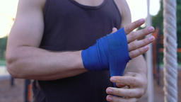 Strong kickboxing man putting on punching wraps and get his palm in fist Footage