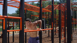 Young topless athlete pushing up on the parallel bars. 50 fps Footage
