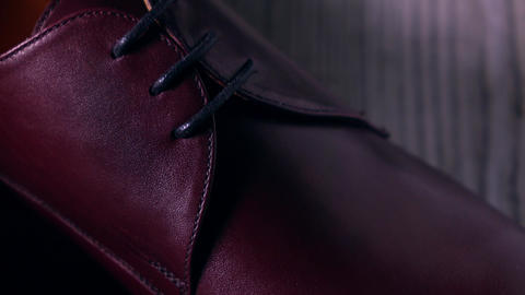 Expensive dark red leather men's footwear 4K pan long shot Live Action