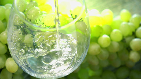 White wine being pored into a glass against bunch of green grapes. Winemaking Footage