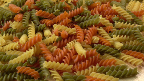 Uncooked three-colored italian pasta. Colored natural pasta Footage