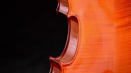 Detail of body of a violin or viola turning at black background Footage
