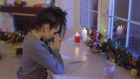 Beautiful girl prays before writing a wish list at the Christmas Footage