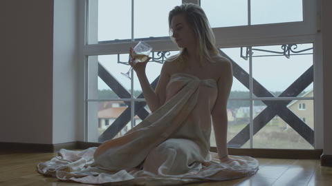 Young naked girl drinks wine sitting on floor near the window Footage