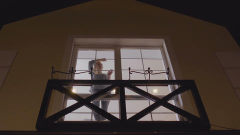 Young girl enjoys evening view from the window Live Action