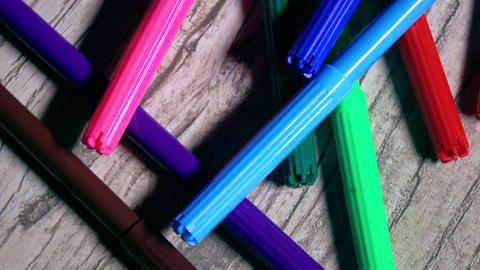 Multicolor markers on wooden table. 4K closeup pan shot Footage