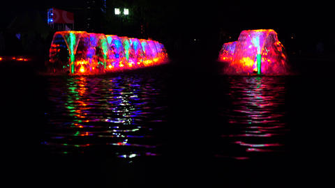 LED lit multicolor fountains at night and reflective water ripple. 4K video Footage