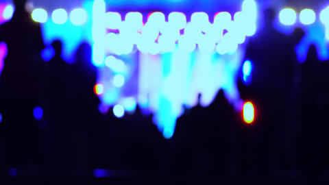 Defocused people silhouettes heading for night show. 4K background bokeh shot Footage