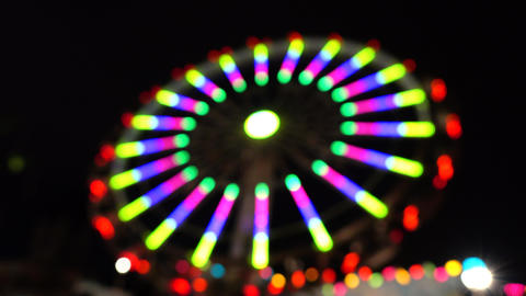 Theme park at night. Defocused spinning LED lit attraction. 4K background bokeh Footage