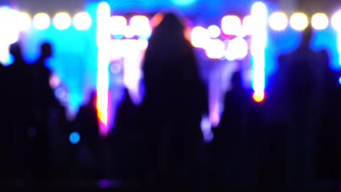Blurred people going to night show. Bright stage lighting. 4K background bokeh Footage