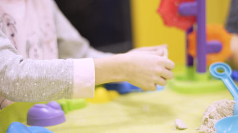 A woman with a daughter from kinetic sand makes figures using shapes. Living Footage