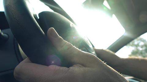Man putting his hands on car steering wheel against blazing sun, 4K video Footage
