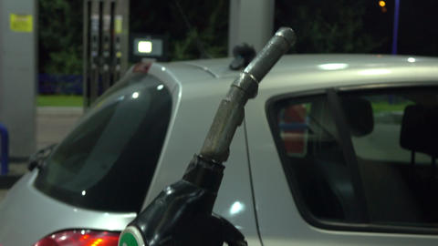 Girl refueling the car at gas station. Inserting and removing filling gun. 4K Live Action