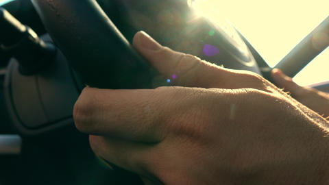 Man putting his hands on leather steering wheel against blazing sun, warm colors Footage