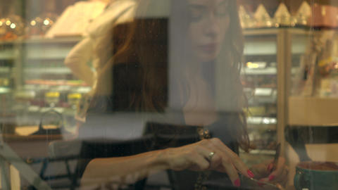 Beautiful brunette girl eating cake in pastry shop. View through window from Footage