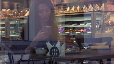 Beautiful brunette girl using her smartphone in cafe. View through window from Footage
