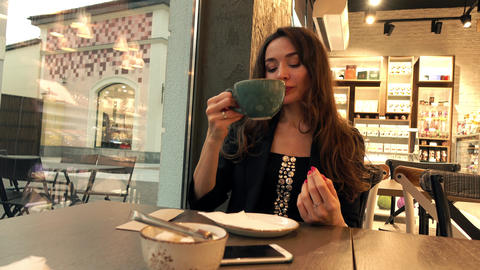 Beautiful caucasian brunette girl drinking hot chocolate in cafe. 4K video Footage