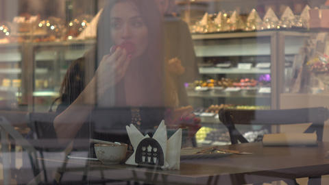 Beautiful brunette young woman eating cake in pastry shop. View through window Footage