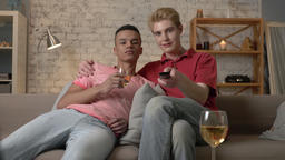 Multinational gay couple sitting on couch, watch funny TV show, laughing, use Footage