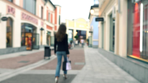 Blurred slim brunette girl in high heels walking with shopping bags by outlet Footage