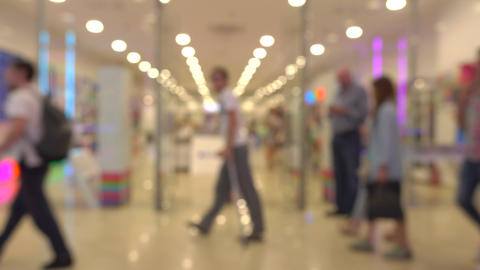Unrecognizable customers walking in modern shopping mall. 4K bokeh shot Footage