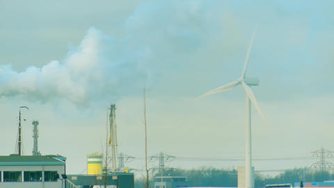 Rotating wind generator and smoke over industrial zone. Clean and dirty energy Live Action