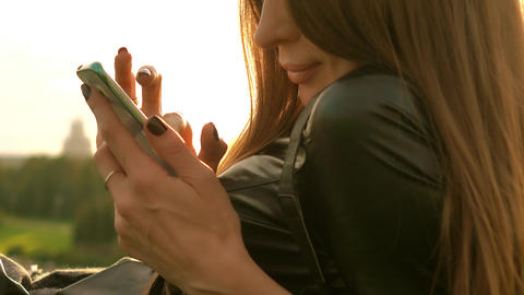 Pretty brunette girl with dark nail polish tapping her mobile phone screen in Footage