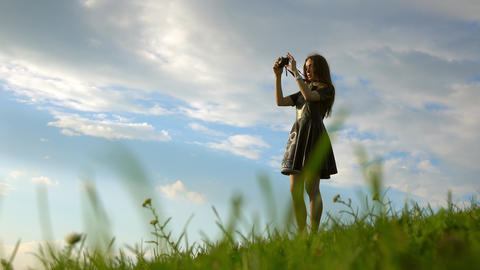 Beautiful brunette girl in black dress standing on the hill and making photos Footage