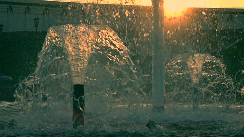 Super slow motion shot of a beautiful park fountain against sunset, orange sun Footage