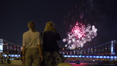 People watching and making photoes of fireworks over bridge. 4K video Footage