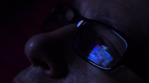 Black rim glasses reflecting glowing tablet touchscreen in dark room, close up Footage