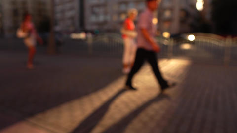Blurred street in the evening. Cars and pedestrians. 4K background bokeh shot Footage