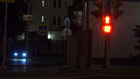 Pedestrian traffic light turns green. Crosswalk at night. 4K shot Footage