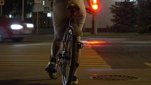 Female biker crossing evening street. Traffic light and crosswalk. 4K shot Footage